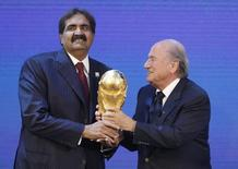 FIFA president Sepp Blatter (R) hands over a copy of the World Cup to Qatar's Emir Sheikh Hamad bin Khalifa al Thani after the announcement that Qatar is going to be host nation for the FIFA World Cup 2022, in Zurich December 2, 2010.        REUTERS/Christian Hartmann