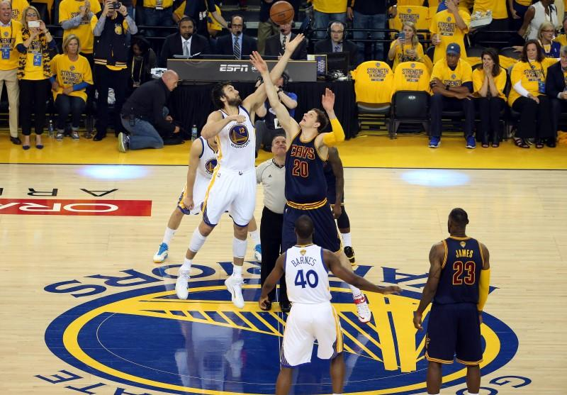 db02820e52d June 4, 2015; Oakland, CA, USA; Golden State Warriors center Andrew Bogut  (12) and Cleveland Cavaliers center Timofey Mozgov (20) both tip off for  the ball ...