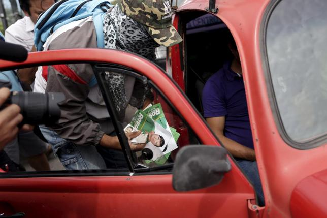 A masked man seizes campaign materials from a car at a checkpoint in Tixtla in the state of Guerrero, June 6, 2015. REUTERS/Jorge Dan Lopez