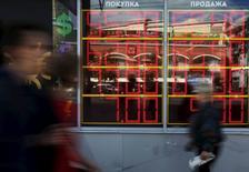 Прохожие у пункта обмена валюты в Москве. 5 июня 2015 года. Рубль вырос при открытии биржевых торгов понедельника после значительного падения его котировок за прошлую неделю, которое участники рынка могли счесть чрезмерно волатильным, а также на фоне снижения градуса напряженности на востоке Украины. REUTERS/Sergei Karpukhin