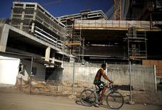 A resident of the Vila Autodromo favela rides his bicycle in front of construction work for the Rio 2016 Olympic Park in Rio de Janeiro, Brazil June 8, 2015.  REUTERS/Pilar Olivares