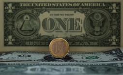Монета евро на фоне долларовой купюры в Мадриде 17 ноября 2011 года. Курс евро растет к доллару за счет улучшения экономической статистики Германии и повышения доходности немецких облигаций. REUTERS/Sergio Perez