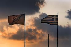 Drapeaux européen et grec sur le toît du ministère des Finances à Athènes. La Commission européenne a reçu une nouvelle proposition de la Grèce susceptible de débloquer de nouveaux financements et est en train de l'étudier. Cette proposition vise à résoudre les derniers différends entre Athènes et ses créanciers internationaux sur des questions telles que les retraites ou la réforme de la TVA. /Photo prise le 5 juin 2015/REUTERS/Yannis Behrakis
