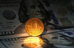 Рублевая монета на фоне долларовых купюр в Санкт-Петербурге 22 октября 2014 года. Рубль начал торги четверга укреплением после роста накануне благодаря отскоку нефтяных цен, однако скоро стал снижаться к доллару, оставаясь стабильным к падающему евро, на фоне отсутствия движения цен черного золота и сохраняющихся рисков в последний торговый день короткой недели в преддверие заседания ЦБР по ставкам в понедельник. REUTERS/Alexander Demianchuk