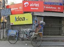 Рикша говорит по сотовому телефону в Калькутте. 3 февраля 2014 года. Российский конгломерат АФК Система начал эксклюзивные переговоры о потенциальном слиянии своего индийского телекоммуникационного бизнеса Sistema Shyam TeleServices Ltd. (SSTL) с четвертым по величине телекоммуникационным оператором Индии Reliance Communications (RCOM), сообщили стороны в понедельник. REUTERS/Rupak De Chowdhuri