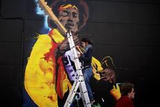 Mulher pinta grafite de Jimi Hendrix em Málaga, na Espanha. 18/02/2015 REUTERS/Jon Nazca