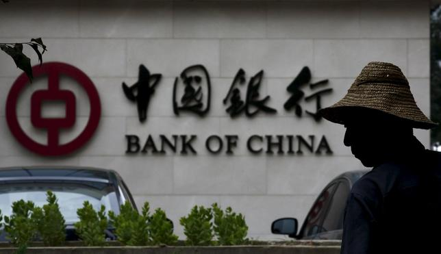 A man is silhouetted in front of a Bank of China's logo at its branch office in Beijing, in this July 14, 2014 file photo.  REUTERS/Kim Kyung-Hoon/Files