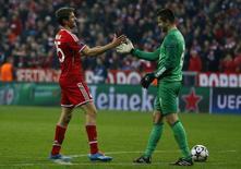 Goleiro do Arsenal Fabianski cumprimentando Mueller, do Bayern de Munique.   11/03/2014          REUTERS/Kai Pfaffenbach
