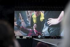 Foo Fighters band member Dave Grohl is seen on a big screen talking on a microphone after falling from the stage during the band's concert at Nya Ullevi in Gothenburg, Sweden, June 12, 2015. REUTERS/Erik Abel/TT News Agency
