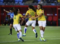 Jun 17, 2015; Moncton, New Brunswick, CAN; Brazil midfielder Raquel (18) celebrates with defender Erika (4) and  midfielder Beatriz (7) after scoring a goal during the second half against Costa Rica in a Group E soccer match in the 2015 FIFA women's World Cup at Moncton Stadium. Mandatory Credit: Matt Kryger-USA TODAY Sports