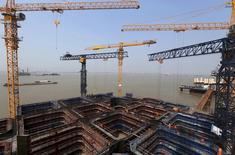 """Краны на месте строительства моста через реку Янцзы в Наньтуне. 25 апреля 2015 года. Китай увеличит """"эффективные инвестиции"""" в ключевых секторах, чтобы поддержать рост, несмотря на то, что видит признаки улучшения экономики, сообщило правительство. REUTERS/China Daily"""