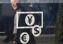 Прохожий отражается в витрине пункта обмена валюты у банка в Токио 27 ноября 2014 года. Курс доллара к корзине шести основных валют близок к месячному минимуму после выхода отчета об инфляции в США. REUTERS/Issei Kato