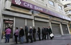 Люди в очереди к банкомату отделения Cyprus Popular Bank (CPB) в Афинах 22 марта 2013 года. Греческие вкладчики вывели из банков более миллиарда евро в четверг, сообщили Рейтер три банковских источника. REUTERS/John Kolesidis