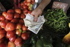 Un hombre muestra billetes de peso cubano, en una mercado en La Habana, 15 de enero de 2015. El esfuerzo por mejorar las relaciones con Estados Unidos parece haber ayudado a la economía comunista de Cuba, donde los funcionarios esperan un crecimiento del 4 por ciento en el primer semestre del 2015, en línea con las proyecciones oficiales. REUTERS/Stringer