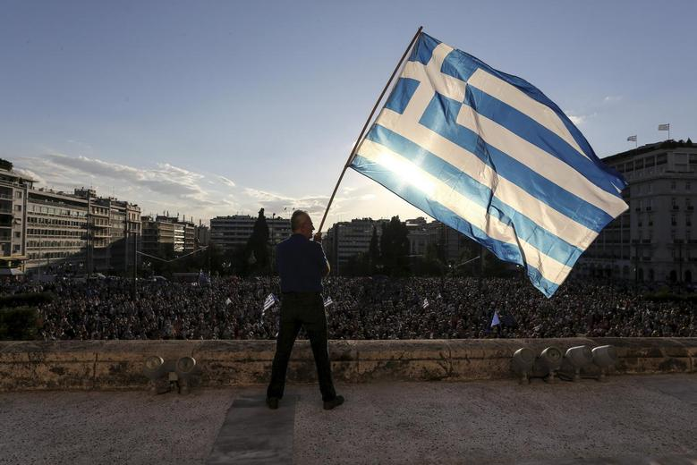 A man waves a Greek national flag while standing at the premises of the parliament building during a rally in front of the parliament building calling on the government to clinch a deal with its international creditors and secure Greece's future in the Eurozone, in Athens, Greece, June 22, 2015. REUTERS/Yiannis Liakos/Intimenews