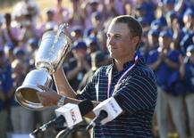 Jun 21, 2015; University Place, WA, USA; Jordan Spieth hoists the U.S. Open Championship Trophy after winning the 2015 U.S. Open golf tournament at Chambers Bay. Mandatory Credit: Michael Madrid-USA TODAY Sports