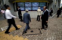 Peatones caminando junto a un tablero electrónico que muestra el índice Nikkei de Japón, y la tasa de cambio entre el yen japonés y el dólar estadounidense, afuera de una agencia de la bolsa, en Tokio, Japón, 23 de junio de 2015. Las bolsas de Asia subían el martes después de que las últimas propuestas presupuestarias de Grecia elevaron las esperanzas de que pueda evitar un impago de su deuda y llegar a un acuerdo con sus acreedores más tarde esta semana. REUTERS/Yuya Shino