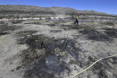A fire fighter look over the crash site of a two-seater single engine S312 Tucano aircraft north of Santa Barbara, California June 23, 2015 in this handout photo provided by the Santa Barbara County Fire Department.  REUTERS/Mike Eliason/Santa Barbara County Fire Department/Handout via Reuters