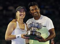 Martina Hingis (L) of Switzerland and Leander Paes of India pose with their trophy after defeating Kristina Mladenovic of France and Daniel Nestor of Canada to win their mixed doubles final match at the Australian Open 2015 tennis tournament in Melbourne February 1, 2015.  REUTERS/Issei Kato