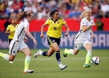 Jun 22, 2015; Edmonton, Alberta, CAN; Colombia forward Lady Andrade (16) moves the ball against United States defender Becky Sauerbrunn (4) and defender Julie Johnston (19) during the second half in the round of sixteen in the FIFA 2015 women's World Cup soccer tournament at Commonwealth Stadium.  Michael Chow-USA TODAY Sports