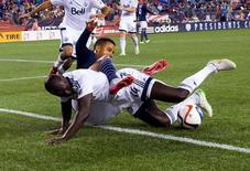 Jun 27, 2015; Foxborough, MA, USA; Vancouver FC defender Pa Modou Kah (44) takes down New England Revolution forward Charlie Davies (9) during the second half of Vancouver FC's 2-1 win over the New England Revolution at Gillette Stadium. Mandatory Credit: Winslow Townson-USA TODAY Sports