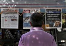 Devant un kiosque à journaux à Athènes, lundi. Les banques grecques resteront fermées à compter de ce lundi et les retraits aux distributeurs automatiques plafonnés à 60 euros par jour dans le cadre des mesures de contrôle des capitaux qu'Alexis Tsipras a ordonnées pour protéger le système bancaire grec d'une vague de retraits massifs susceptibles d'entraîner la faillite des établissements bancaires. /Photo prise le 29 juin 2015/REUTERS/Yannis Behrakis