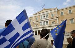 Manifestation pro-euro à Athènes. L'Eurogroupe des ministres des Finances de la zone euro se réunit mardi soir par téléconférence pour discuter d'une demande de dernière minute de la Grèce portant sur une extension de son programme de sauvetage. /Photo prise le 30 juin 2015/REUTERS/Yannis Behrakis