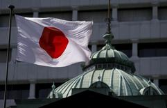 Una bandera japonesa ondea sobre el edificio del Banco de Japón, en Tokio, 22 de mayo de 2015. La confianza de los empresarios japoneses mejoró a niveles no vistos desde antes de que la economía entró en recesión el año pasado, ofreciendo alivio a las autoridades que desean mantener la recuperación intacta sin estímulos adicionales. REUTERS/Toru Hanai