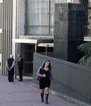 Una mujer camina frente al Banco Central de Uruguay, en el distrito financiero de Montevideo, 20 de agosto de 2014. El déficit fiscal uruguayo sumó 45.453 millones de pesos (unos 1.679 millones de dólares) en los últimos 12 meses a mayo, que equivale a un 3,3 por ciento del Producto Interno Bruto (PIB), empeorando en la comparación interanual pero recuperándose respecto al dato hasta abril, dijo el Gobierno. REUTERS/Andres Stapff
