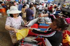 Una mujer vende pescado en el mercado de Villa María del Triunfo, a las afueras de Lima, 30 de marzo de 2015. La producción del vital sector de minería e hidrocarburos en Perú subió un 1,49 por ciento interanual en mayo ante el repunte de la actividad extractiva de metales como el cobre y el oro, mostraron el miércoles indicadores adelantados del Gobierno. REUTERS/Mariana Bazo