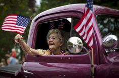 A woman waves an American flag as she rides in an antique pickup truck through Barnstable Village on Cape Cod, during the annual Fourth of July Parade celebrating the country's Independence Day, in Barnstable, Massachusetts, July 4, 2015. REUTERS/Mike Segar