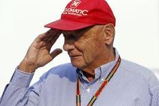 Austrian Formula One legend Niki Lauda salutes as he walks in the paddock ahead of the Singapore F1 Grand Prix at the Marina Bay street circuit in Singapore September 21, 2014.  REUTERS/Xavier Galiana