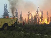 Firefighters tackle a wildfire near the town of La Ronge, Saskatchewan July 4, 2015 in a picture provided by the Saskatchewan Ministry of Government Relations.   REUTERS/Saskatchewan Ministry of Government Relations/Handout via Reuters