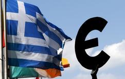 Флаг Греции на фоне символа валюты евро в Брюсселе 6 июля 2015 года. Греция во вторник получит последний шанс остаться в еврозоне, когда премьер-министр Алексис Ципрас представит новые предложения на экстренном саммите еврозоны, после того, как греческие избиратели отвергли условия программы помощи, предложенной кредиторами. REUTERS/Francois Lenoir