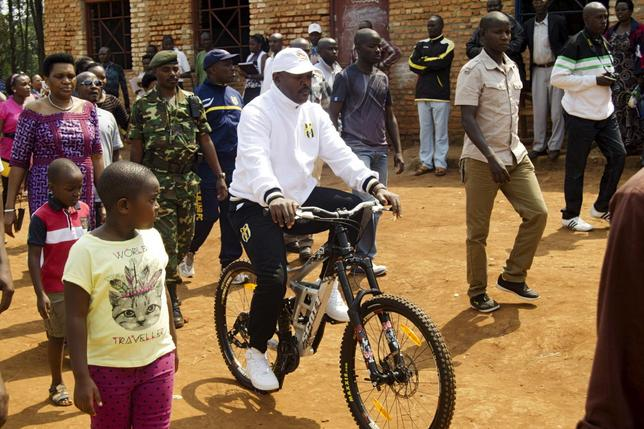 President Pierre Nkurunziza rides a bicycle as he heads to the venue where he voted in at a polling station in his rural home in Ngozi during a parliamentary election in Burundi June 29, 2015.   REUTERS/Stringer