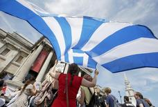 A woman holds the flag of Greece at the 'Greek solidarity festival' in Trafalgar Square, London, Britain, July 4, 2015.  REUTERS/Peter Nicholls