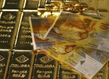 Barras de oro y billetes de francos suizos, en esta ilustración fotográfica tomada en Viena, 7 de noviembre de 2014. El oro subía el miércoles por un retroceso del dólar, aunque los precios se mantenían rondando el mínimo en cuatro meses que alcanzó más temprano en la sesión ante el nerviosismo de los mercados por el desplome de la bolsa china y el desarrollo de la crisis de deuda griega. REUTERS/Leonhard Foeger
