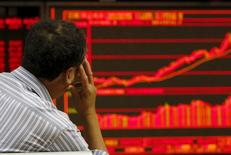 Un inversor mira un tablero electrónico que muestra la información de las acciones en una correduría en Beijing, 9 de julio de 2015. Las acciones chinas rebotaron con fuerza el jueves, y el índice compuesto de Shanghái registró su mayor ganancia porcentual en seis años luego de que una nueva ronda de medidas de apoyo del Gobierno frenó las ventas por el pánico. REUTERS/Kim Kyung-Hoon