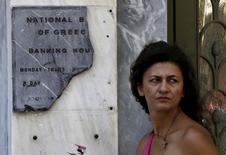 Una mujer junto a una placa rota del Banco Nacional de Grecia, en Atenas, 8 de julio de 2015. Algunos grandes bancos griegos podrían verse forzados a cerrar o ser absorbidos por rivales más fuertes como parte de la reestructuración del sector que se produciría tras un rescate del país, dijeron funcionarios europeos a Reuters. REUTERS/Yannis Behrakis