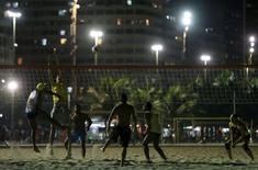 Residents play beach volleyball during at night on Copacabana beach, where the Olympic beach volleyball will take place in Rio de Janeiro, Brazil, July 9, 2015.  REUTERS/Sergio Moraes
