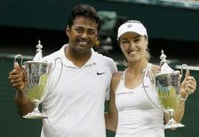 Leander Paes of India and Martina Hingis of Switzerland show off their trophies after winning their Mixed Doubles Final match against Timea Babos of Hungary and Alexander Peya of Austria at the Wimbledon Tennis Championships in London, July 12, 2015.   REUTERS/Stefan Wermuth