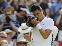 Bernard Tomic of Australia leaves the court after losing his match against Novak Djokovic of Serbia at the Wimbledon Tennis Championships in London, July 3, 2015.             REUTERS/Suzanne Plunkett