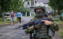 Women walk towards a Ukrainian government serviceman searching for members of Right Sector in the village of Bobovyshche near Mukacheve, Ukraine, July 13, 2015. Kiev has called on Right Sector, which played a prominent role in protests that toppled Moscow-backed President Viktor Yanukovich a year ago, to lay down their weapons after a shootout on Saturday in the town of Mukacheve killed at least two people.  REUTERS/Stringer