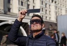 Фабио Капелло наблюдает частичное солнечное затмение в Москве. 20 марта 2015 года. Российский футбольный союз и тренер сборной РФ Фабио Капелло достигли соглашения о прекращении контракта, говорится в сообщении на сайте РФС. REUTERS/Maxim Zmeyev