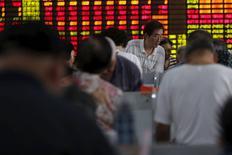 Inversores miran la pantalla de computadores frente a un tablero electrónico que muestra la información de las acciones, en una correduría en Shanghái, China, 14 de julio de 2015. Los índices de acciones de China cayeron el martes, luego de tres días de rebote, después de que una fuerte corrección en los valores de primer orden contrarrestó las ganancias en los papeles de menor capitalización. REUTERS/Aly Song