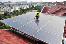 Trabalhador inspeciona painéis solares no teto de um edifício residencial em Yichang, na provícia chinesa de Hubei 16/09/ 2013.   REUTERS/Stringer