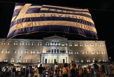 Manifestantes que se oponen a las medidas de austeridad levantan una bandera frente al Parlmento griego en Atenas, Grecia. 15 de julio, 2015. El Parlamento de Grecia aprobó el paquete de medidas de austeridad demandado por los socios europeos para iniciar las conversaciones para un nuevo rescate, que Atenas necesita para evitar la bancarrota y mantenerse dentro de la zona euro, horas después de un violento choque entre manifestantes y la policía. REUTERS/Yiannis Kourtoglou