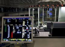 Una persona filma un tablero electrónico que muestra el índice Nikkei y otros índices, visto junto a un computador que muestra los índices de la Bolsa de Tokio, en Tokio, Japón, 9 de julio de 2015. La mayoría de las bolsas en Asia subía el jueves después de que Grecia aprobó un plan de rescate y generó un alivio leve, y el dólar avanzaba luego de que la presidenta de la Reserva Federal, Janet Yellen, reforzó las expectativas de un alza en las tasas de interés en Estados Unidos. REUTERS/Yuya Shino