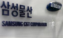 Employees are reflected on a logo of Samsung C&T Corp at the company's headquarters in Seoul, South Korea, July 16, 2015.  REUTERS/Kim Hong-Ji