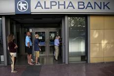 En la imagen de archivo, algunas personas hacen fila frente a un cajero automático fuera de una sucursal de Alpha Bank en Atenas, Grecia, el 15 de julio de 2015. El Gobierno griego ordenó a los bancos que vuelvan a abrir el lunes 20 de julio, tres semanas después de que cerraron para impedir que el sistema colapsara bajo una ola de retiros, mientras que el primer ministro Alexis Tsipras contemplaba el inicio de nuevas negociaciones para un rescate la próxima semana.  REUTERS/Yiannis Kourtoglou - RTX1KC0W